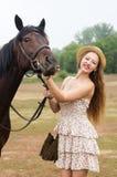 草帽的轻头发的女孩和夏天穿戴摆在与马 免版税库存图片