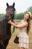 草帽的轻头发的女孩和夏天穿戴,拍摄与马 免版税库存图片