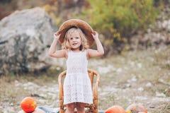 草帽的迷人的小女孩,藤椅,南瓜 免版税库存照片