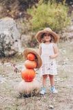 草帽的迷人的小女孩,藤椅,南瓜 库存照片