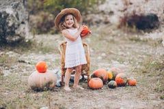草帽的迷人的小女孩,藤椅,南瓜 免版税图库摄影