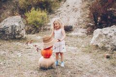 草帽的迷人的小女孩,藤椅,南瓜 图库摄影