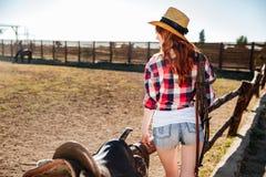 草帽的年轻女牛仔马鞍为乘驾做准备 免版税图库摄影