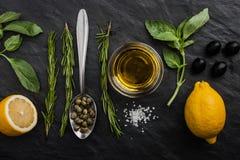 草本与柠檬、雀跃和橄榄混合在黑石桌上 库存图片