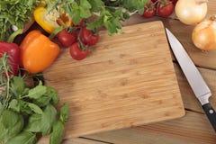 草本和菜与一块空白的砧板 复制的空间 免版税库存图片