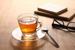草本热的茶在一个木地板安置的一块清楚的玻璃安置 库存照片