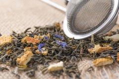 草本绿茶干叶子增加柑橘果皮和蓝色花的 免版税库存图片