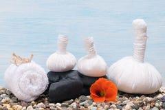 草本袋子和毛巾与石头按摩的 免版税库存照片