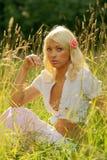 草甸坐的夏天晴朗的妇女年轻人 免版税库存图片
