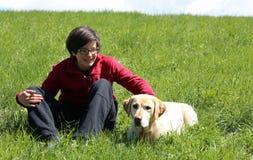 草甸的微笑的年轻男孩有黄色拉布拉多猎犬的 免版税库存照片