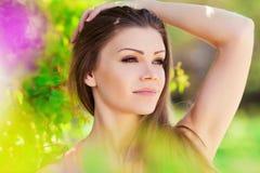 草甸的美丽的年轻深色的妇女有白花的在一个温暖的夏日 免版税库存图片
