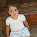 草甸的逗人喜爱的小女孩 免版税库存图片