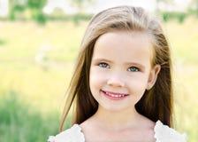 草甸的逗人喜爱的微笑的小女孩 库存图片