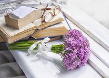 草甸花、旧书和玻璃花束在一块木窗口基石 免版税库存照片