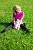 草的兴高采烈的女孩用玩具兔子 免版税库存照片