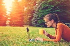 草的女孩使用膝上型计算机键入 免版税图库摄影