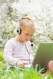 草的女孩孩子与耳机和膝上型计算机 图库摄影