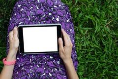 草的妇女与片剂 免版税库存图片