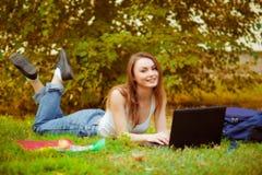 草的学生女孩与计算机 库存照片