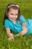 草的微笑的小女孩 图库摄影