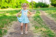 绿草的快乐的小女孩 库存图片