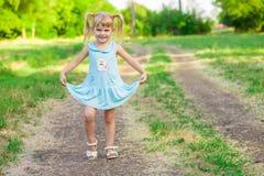 绿草的快乐的小女孩 免版税库存照片