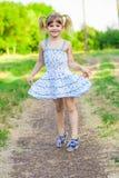 绿草的快乐的小女孩 库存照片