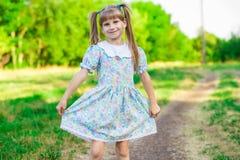 绿草的快乐的小女孩 免版税图库摄影
