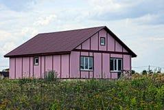 草的现代紫罗兰色房子反对天空 免版税库存图片