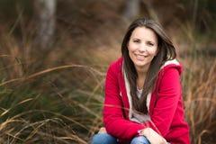 草的美丽的微笑的妇女 免版税图库摄影