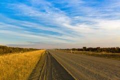 草的金黄颜色沿开启的石渣路,高地湖的 免版税库存照片