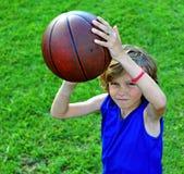 草的年轻蓝球运动员 库存照片