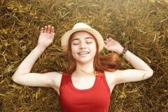 草秋天的逗人喜爱的愉快的女孩 免版税库存图片