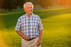 草背景的老人 免版税图库摄影