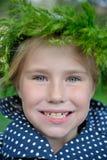 草花圈的特写镜头画象愉快的小女孩 免版税库存图片