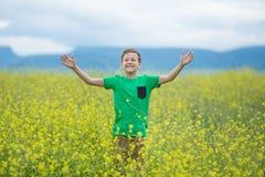 绿草草坪的愉快的逗人喜爱的英俊的小孩男孩用开花的黄色蒲公英在晴朗的春天或夏日开花 littl 免版税库存图片