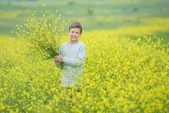 绿草草坪的愉快的逗人喜爱的英俊的小孩男孩用开花的黄色蒲公英在晴朗的春天或夏日开花 littl 免版税图库摄影
