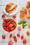 草莓、新近地被烘烤的新月形面包和奶油 库存图片