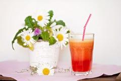 草莓、桔子和苹果新鲜在与被排行的秸杆的一块玻璃 免版税图库摄影