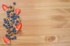 草莓、蓝莓和坚果在木背景 库存图片
