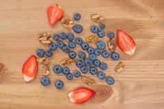 草莓、蓝莓和坚果在木背景 库存照片