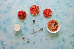 草莓、muesli、牛奶和土耳其快乐糖在绿松石桌上 早餐匙子展示时间的时刻 免版税库存图片