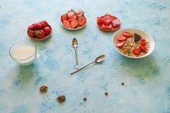 草莓、muesli、牛奶和土耳其快乐糖在绿松石桌上 早餐匙子展示时间的时刻 免版税图库摄影