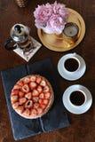 草莓乳酪蛋糕,咖啡在法国新闻,白色杯子,在一个滑稽的花瓶的桃红色牡丹,在盘子的金黄烛台中 图库摄影