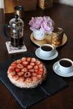 草莓乳酪蛋糕,咖啡在法国新闻,白色杯子,在一个滑稽的花瓶的桃红色牡丹,在盘子的金黄烛台中 库存图片
