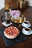草莓乳酪蛋糕,咖啡在法国新闻,白色杯子,在一个滑稽的花瓶的桃红色牡丹,在盘子的金黄烛台中 库存照片