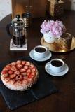 草莓乳酪蛋糕,咖啡在法国新闻,白色杯子,在一个滑稽的花瓶的桃红色牡丹,在盘子的金黄烛台中 免版税库存照片