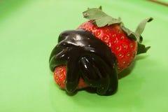 草莓冠上了用在绿色板材的巧克力糖浆 库存照片