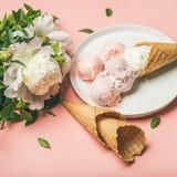 草莓和椰子饯奶油,奶蛋烘饼锥体,白色牡丹开花 免版税库存图片