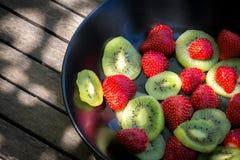 草莓和猕猴桃在一个黑色的盘子 库存照片